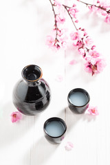 Sake in old black ceramics on white table