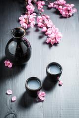 Unfiltered sake in dark ceramics and blooming flowers