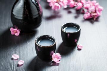 Closeup of sake in black ceramics and blooming flowers