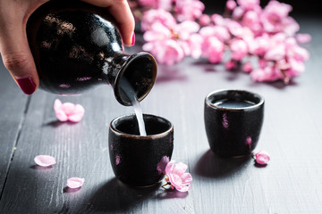 Pouring sake to dark ceramics on black table