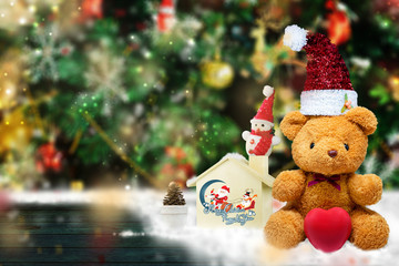 Teddy Bear wearing red hat is placed on a wooden table, with a wooden house, a snowman and a backdrop of green trees adorned with decorative items. Celebrate Christmas And happy new year