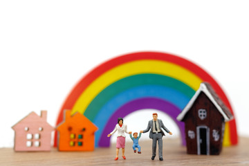 Miniature people: family and children enjoy with house and rainbow, happy family day concept.