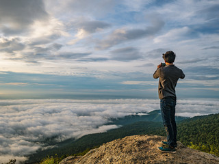 People Take a Picture on the cliff with beautiful sunrise sky on Khao Luang mountain in Ramkhamhaeng National Park,Sukhothai province Thailand