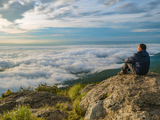 Asian men Sit on the cliff with beautiful sunrise sky on Khao Luang mountain in Ramkhamhaeng National Park,Sukhothai province Thailand