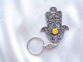 A key ring in the form of Fatima Hand on a white silk background. Ancient symbol and traditional modern tourist souvenir of Tunisia.