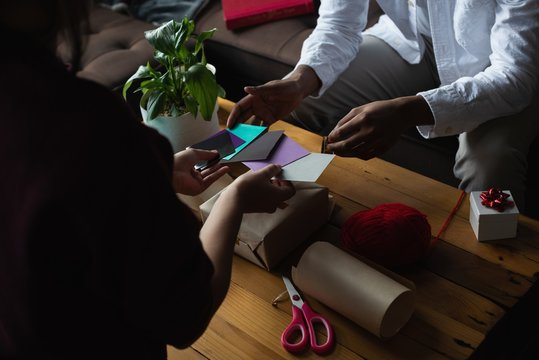 Couple choosing gift tag in living room