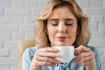 smiling businesswoman with closed eyes holding cup of coffee at workplace
