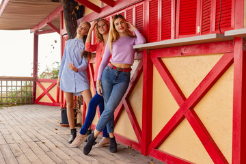 Portrait of three young female friends on the background of a red wooden wall
