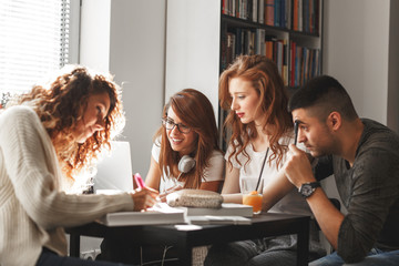 Group of students study in the school campus library.Learning and preparing for university exam.