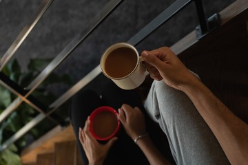 Couple holding coffee in stairs at home