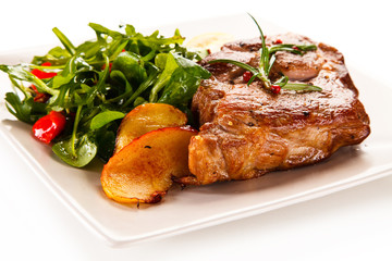 Grilled beefsteak with vegetable salad and apples