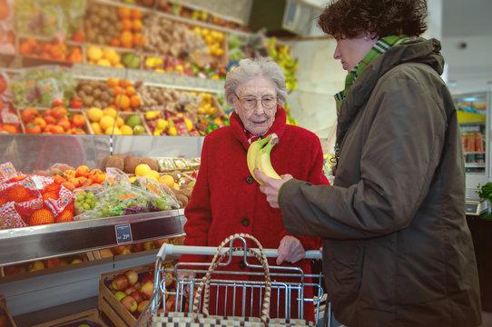 Seniorin im Supermarkt mit Betreuerin