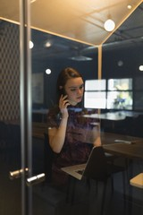 Businesswoman talking on mobile phone at desk