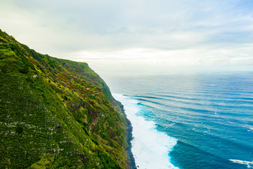 Aerial view of the ocean island cliffs with huge white waves and crystal blue water