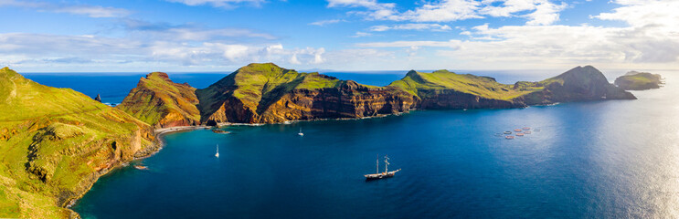 Aerial tropical island view in the middle of the ocean with rocky cliffs and green fields Fototapete