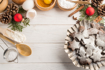 Freshly baked homemade Christmas cookies on a wooden white background with copy space. Top view.