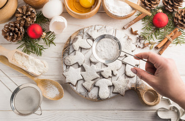 Freshly baked homemade Christmas cookies with sugar powder on a wooden white background with copy space. Flat lay.