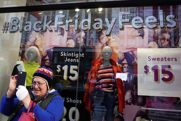 A woman takes a photo during Black Friday shopping in New York City,