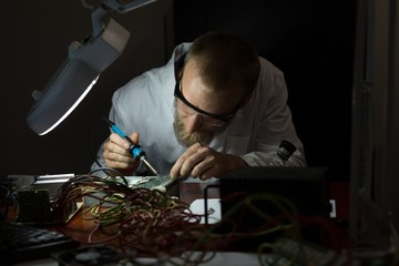 Robotics engineer assembling circuit board at desk