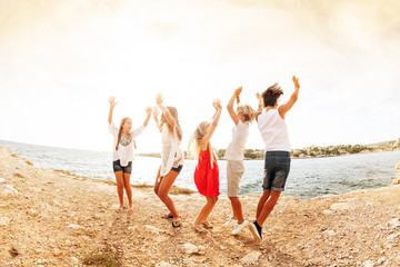 Joyful teens dancing and jumping at the seaside
