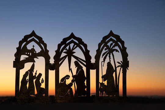 Silhouette photograph of a Christmas nativity scene against the sunset