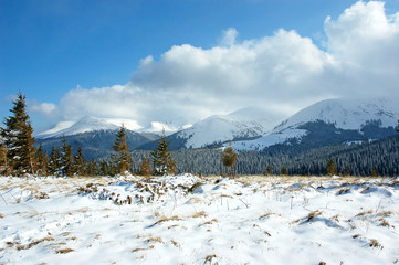 Winter mountain landscape with snow covered road forest hills snow and blue sky with clouds