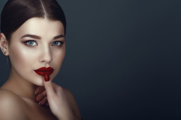 Close up portrait of beautiful dark-haired model with perfect make up and centre part sleek bun touching her ideal shaped lips with manicured finger. Isolated on grey background. Text space