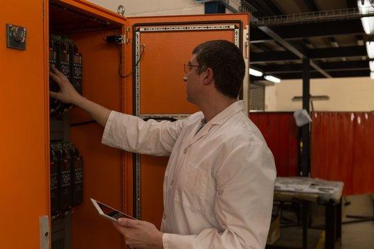 Robotics engineer examining control panel