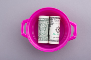 One dollar paper currency in pink pot