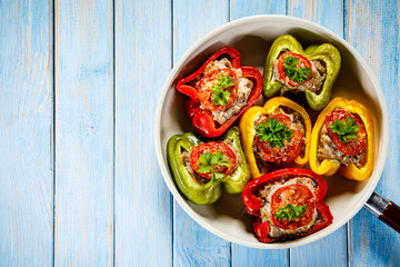 Stuffed peppers in frying pan on wooden table