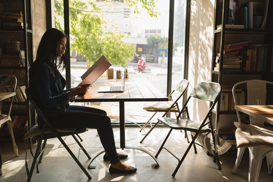 Woman looking at menu while sitting in cafe