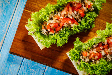 Sandwiches with meat and vegetables on cutting board