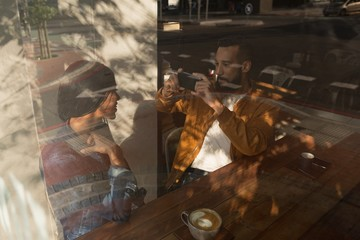 Man taking photo of woman in cafe
