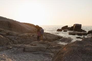 Couple walking on rock near sea side