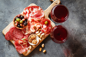 Top view of meat plate, cold smoked pork, jamon, prosciutto, salami served with wine, nuts and olives from above
