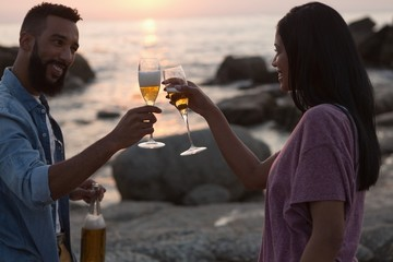Couple toasting champagne glass near sea side