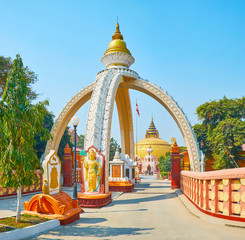 SAGAING, MYANMAR - FEBRUARY 21, 2018: The scenic stupa-shaped gate of Sitagu International Buddhist Academy with fine plasterwork, golden spire and main pagoda on background, on February 21 in Sagaing