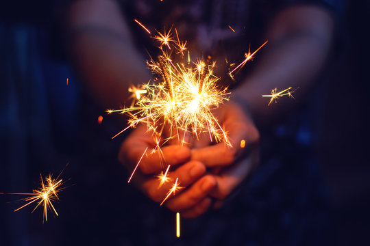 Woman hand holding a burning sparkler, Christmas and new year sparkler holiday background