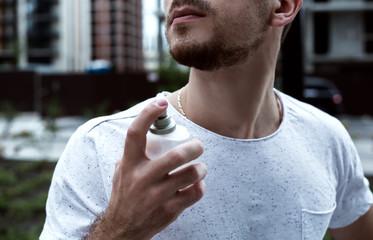Guy sprays perfume on his body