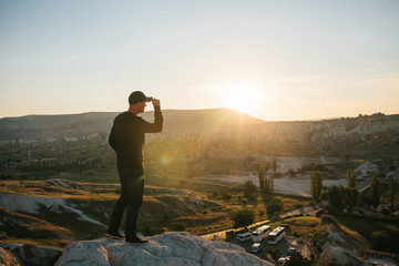 A man stands on top of a mountain in solitude, admires the beautiful view of the natural landscape in Cappadocia in Turkey