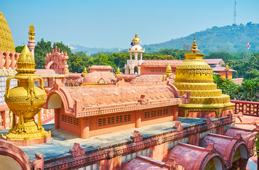 The terracotta roofs, golden stupa and decorative details of the Sitagu International Buddhist Academy pagoda, located at the foot of Sagaing Hill, Myanmar.