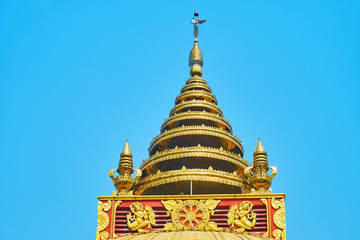 The golden multi-staged hti umbrella of Sitagu International Buddhist Academy pagoda with relief decorative details and ringing bells, Sagaing, Myanmar.