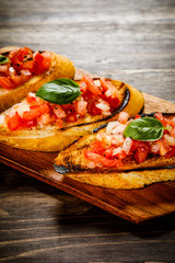 Bruschettas on cutting board on wooden background