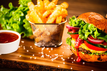 Tasty burger with chips served on cutting board
