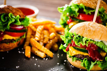 Tasty cheeseburgers with french fries served on black stone