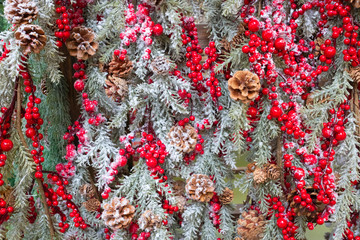 Christmas background with fir branches, pine cones, red berries and snow