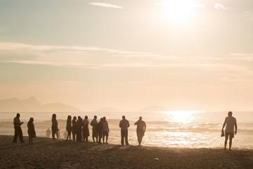 group of tourists enjoying sunshine on the sand of Copacabana beach in rio de janeiro