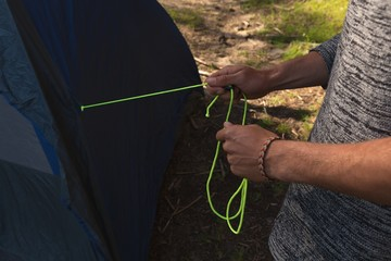Man putting up a tent in the forest