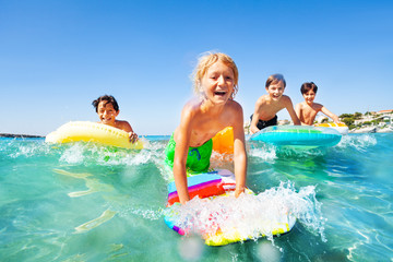 Happy boy riding the waves with his friends