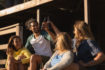 Group of friends toasting beer bottle on cabin